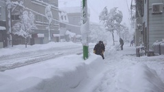 People Shovel Snow From Sidewalk During Blizzard Stock Footage
