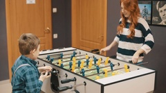 Mom and son playing table soccer Stock Footage