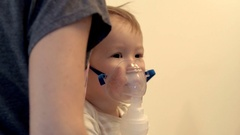 Close view of little baby with inhaler mask on his face over mother's shoulder Stock Footage