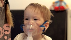 Little baby boy is breathing through the transparent inhaler mask. He quietly Stock Footage