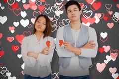 Composite image of young couple holding broken heart Stock Photos