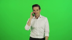 A young businessman answering a call, talks happily and hangs while walking. Stock Footage
