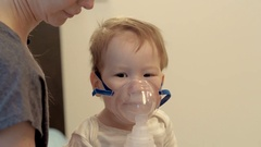 Close portrait of infant two year ill boy with inhalation device. Illness in Stock Footage