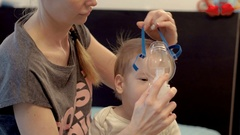 Young mother in casual clothes puts inhaler mask on her little ill baby's face Stock Footage