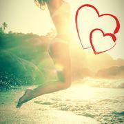 Beautiful jumping blond in white bikini at beach Stock Photos