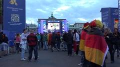 4K Group football fans celebrate at Brandenburg Gate support soccer team Berlin Stock Footage