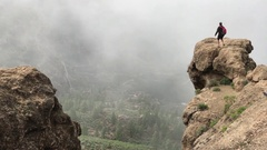 Man walking at a rock at the Roque Nublo Stock Footage