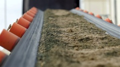 Shallow DOF. Slow motion of conveyor belt transporting building material. Stock Footage
