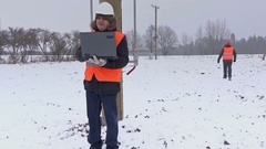 Electrician under high-voltage lines in winter Stock Footage