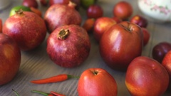 Fresh fruits lies on wodden table: apple, pomegranate, chilli, lime, plum in the Stock Footage