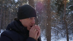 The man in the hat breathes on hands in winter forest Stock Footage