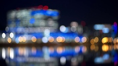 Rack focus of buildings reflecting on Tempe Town Lake at night Stock Footage