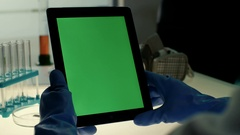 Scientist holding and working with tablet PC with green screen in modern Stock Footage