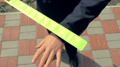 Boy in school uniform put on himself and the girl reflector safety snap band Stock Footage