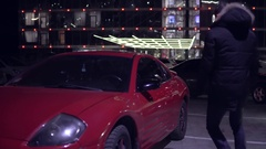 Man getting into red sport car on drivers side. City lights at night on the Stock Footage