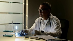 Senior doctor in medical gown or robe with stethoscope working with his computer Stock Footage