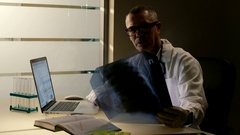 Elderly doctor looks at X-ray scan of human thorax. Medical man checks patient's Stock Footage
