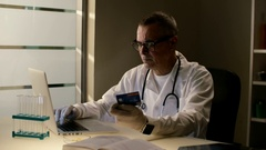 Elderly doctor in medical gown or robe with stethoscope works at his laptop and Stock Footage