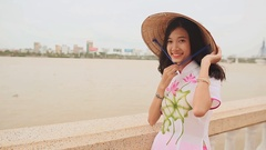 Vietnam girl in the national costume and dress Ao Dai posing on the waterfront Stock Footage
