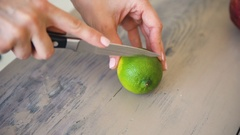 Human hands cutting a slice of lime in pieces for preparing mojito cocktail in Stock Footage