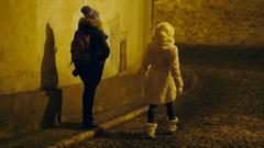 Two girls walking on an empty street in Prague Stock Footage
