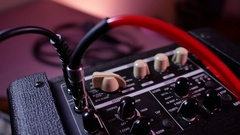Man's hand removes the cable jack from guitar amp Stock Footage
