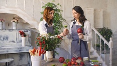 Two young handsome chef florists work at flowers fruit shop making fruit and Stock Footage