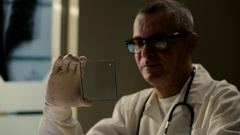 Elderly experienced doctor with futuristic hologram hud tablet. Shot was made Stock Footage