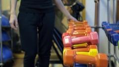 Sportswoman choose dumbbells to train in sport gym Stock Footage