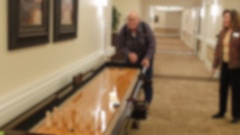 An older man plays shuffle board in a retirement home Stock Footage