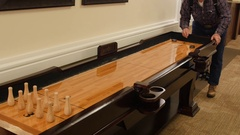 An older man plays shuffle board in retirement home Stock Footage
