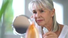 Portrait of senior woman applying anti-aging cream Stock Footage