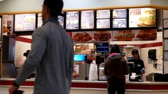 Motion of people ordering food at Arby's check out counter inside mall Stock Footage