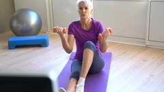 Senior woman doing fitness exercices in front of tv Stock Footage