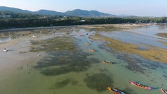 Low tide on the Rawai beach during sunset. Traditional thai long-tail boats in Stock Footage