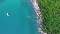 Small yacht in clear blue water next to secret Nui beach with with stones and Stock Footage