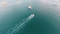 Camera follow the inflatable motor boat betweet sailboats near small Islands. HD Stock Footage