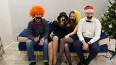 Four friends in clown headwear sit at sofa, shake heads then clap hands together Stock Footage