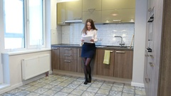 Woman review printed document, stand at kitchen, take cup and drink tea Stock Footage