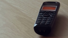 Cordless landline telephone receiver ringing on the table Stock Footage