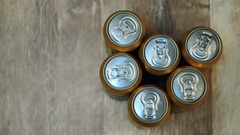 Six beer cans on wooden table, top view Stock Footage