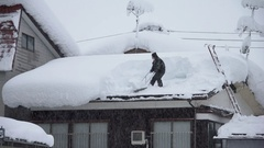 Man Clears Deep Snow From Roof During Blizzard Stock Footage