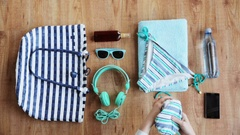 Hands packing beach accessories to bag Stock Footage