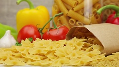 Pasta on background of fresh vegetables and spices Stock Footage