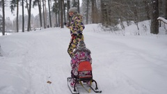 Young mother runs on a snowy pine park, holding  rope from the sled,  which h Stock Footage