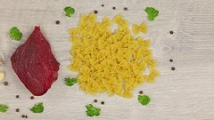 Fresh food on gray background, meat, pasta and vegetables Stock Footage