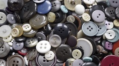 Top view of many buttons of different colors and shapes rotating. Stock Footage