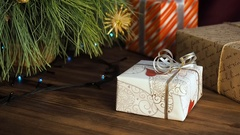Boxes of gifts are under the tree. Gifts are Packed in colorful paper and tied Stock Footage