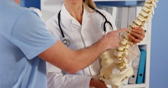 Physiotherapist explaining the spine to male patient Stock Footage