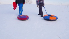 The family rises to snowy hill with snowtube.slow motion. snow winter landscape Stock Footage